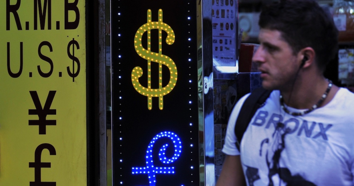A westerner walks past a currency exchange shop in Hong Kong.</p>