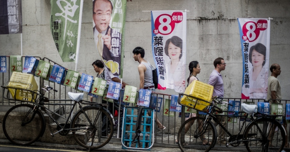 Pedestrians walk past election flags displayed in a street of Hong Kong on September 9, 2012. Beijing is under pressure as calls for full democracy grow and disenchantment with Chinese rule surges ahead of the 2017 election of a chief executive, which the mainland government has promised will be decided with universal suffrage.</p>