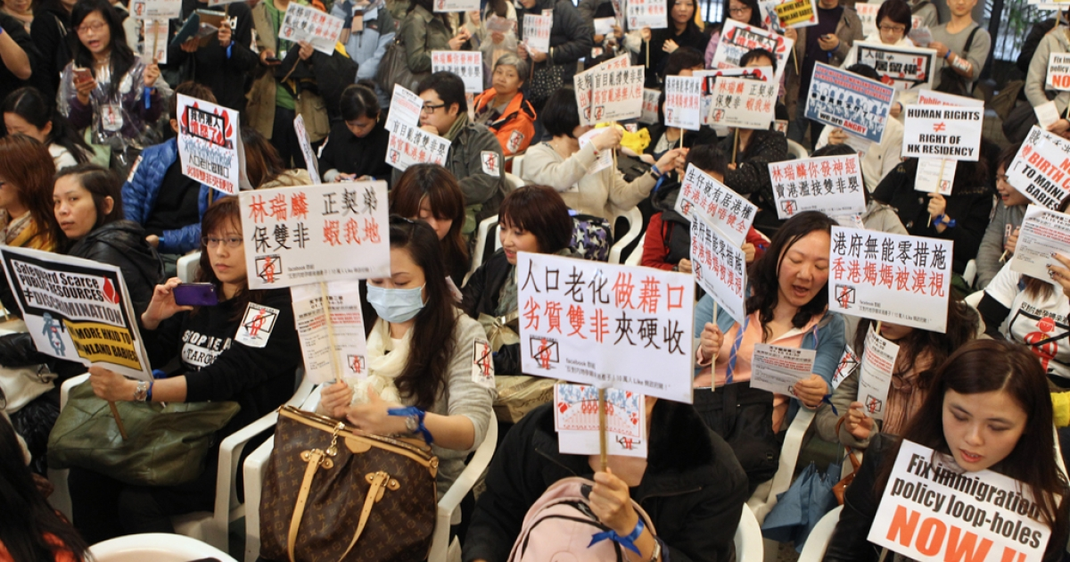 Hong Kong women hold placards during a demonstration in Hong Kong on January 15, 2012. The demonstration was held to oppose the growing number of mainland Chinese women giving birth in the city.  AFP PHOTO/Joyce WOO</p>