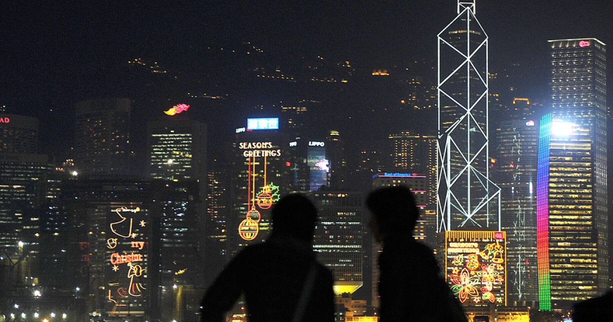 Two people stand across the Kowloon peninsula in Hong Kong. Hong Kong was named this years top financial market developer by the World Economic Forum, beating out New York and London.</p>