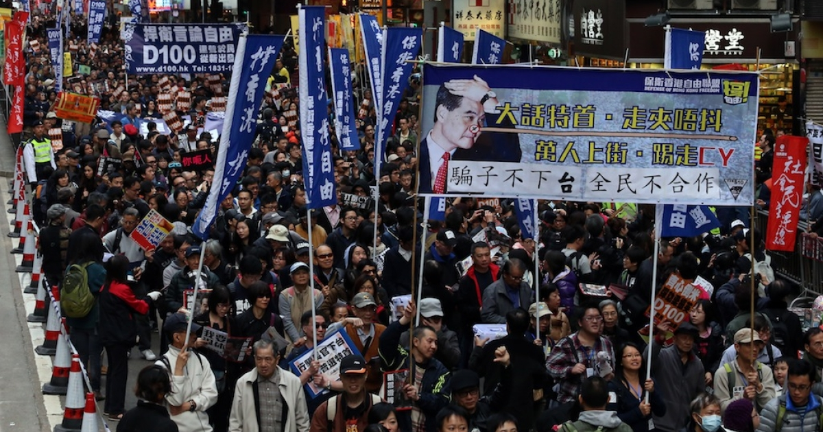 Protesters holding a banner with a picture of Hong Kong chief executive Leung Chun-ying as 'Pinocchio' take part in a pro-democracy rally in Hong Kong on January 1, 2013. Tens of thousands of protesters took to the streets, calling for the city's embattled leader to quit and demanding greater democracy 15 years after it returned to Chinese rule.</p>