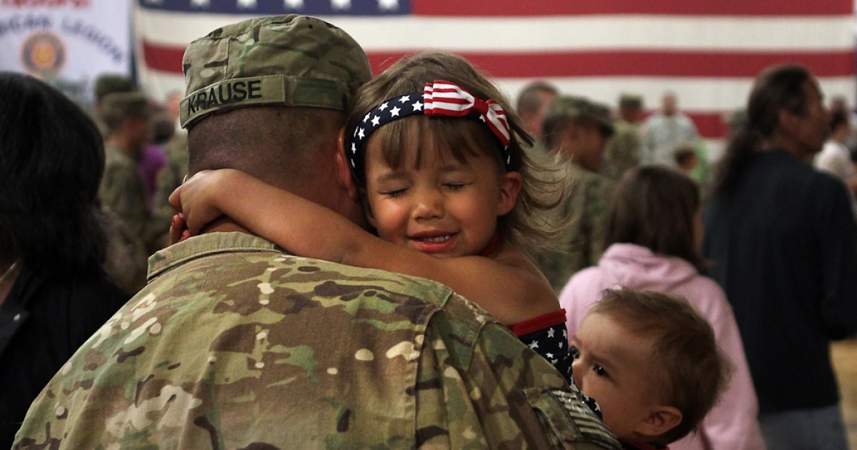 Reniah Krause, 2, clings to her father Sgt. Joseph Krause after he and fellow soldiers arrived from Afghanistan to Fort Carson, Colorado. June 15, 2011. More than 500 soldiers from the 1st Brigade Combat Team returned home following a year of heavy fighting in Afghanistan.</p>