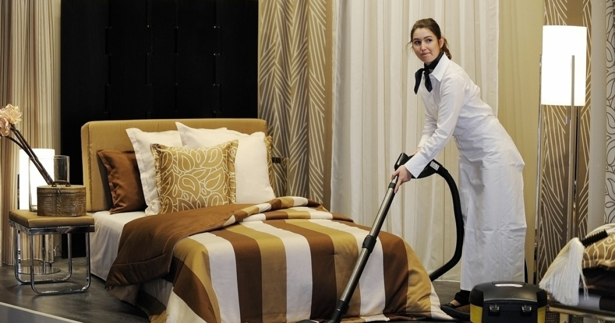 A woman uses a vacuum cleaner to clean and prepare a stand at the 'Home Textiles' trade fair in Frankfurt, Germany on January 12, 2010.</p>