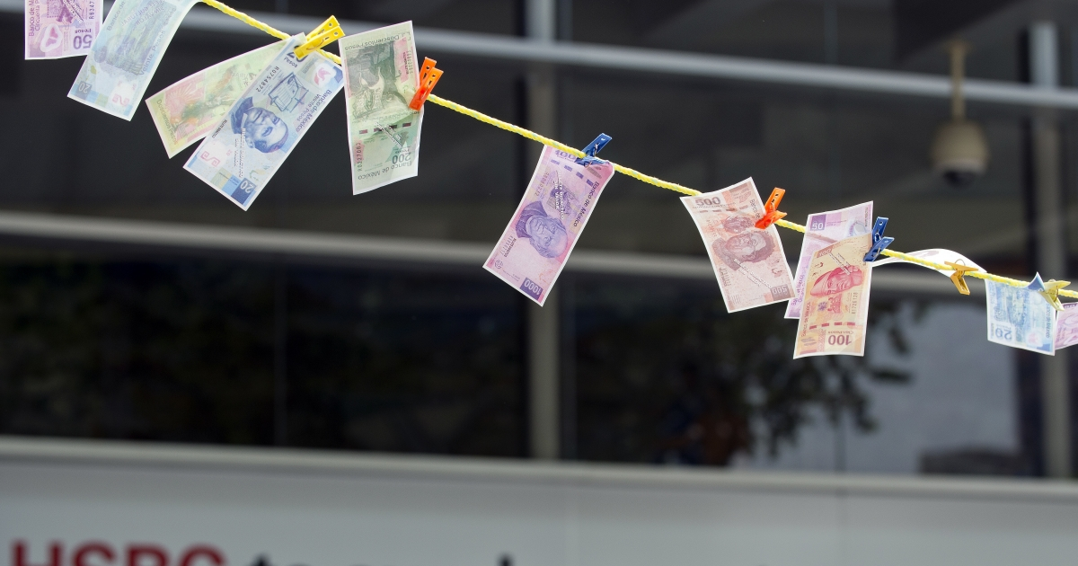 Fake notes were hung out to dry during a protest in front of HSBC in Mexico City on July 30. The bank was fined for failing to apply anti-money laundering rules.</p>