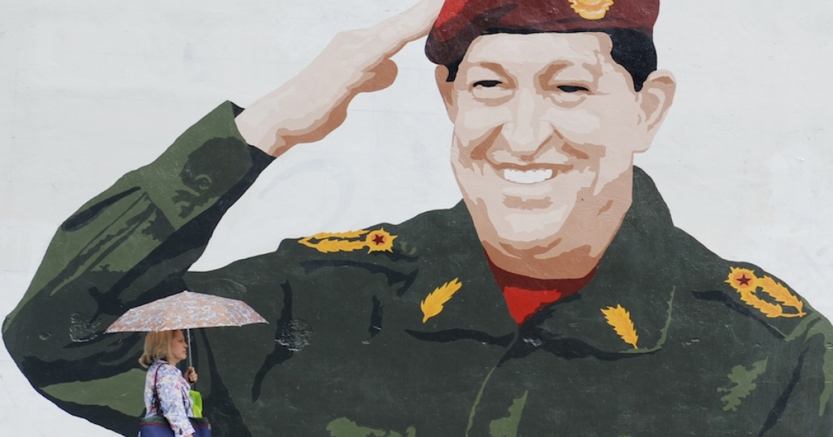 A woman walks by graffiti depicting Venezuelan President Hugo Chavez in Caracas on April 24, 2012.</p>