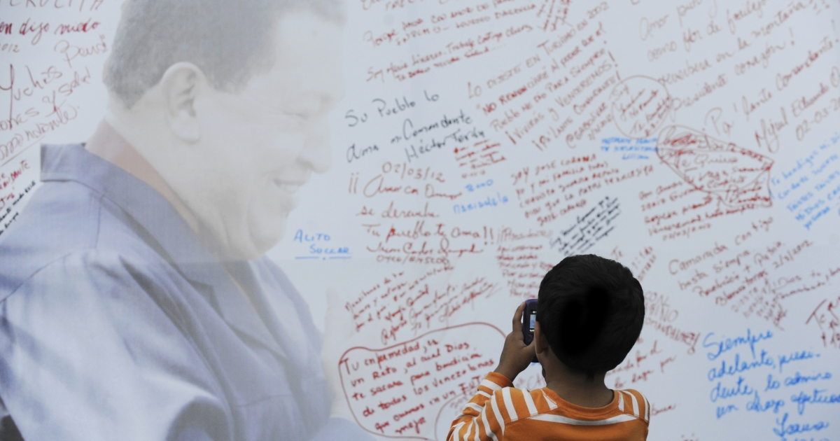 A boy takes pictures of a poster with the image of Venezuelan President Hugo Chavez in Caracas.</p>