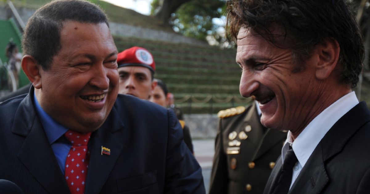 Venezuelan President Hugo Chavez (L) jokes with US actor Sean Penn during his visit to Miraflores presidential palace in Caracas, on February 16, 2012. The Venezuelan government denied rumors that Chavez had to go to Cuba for emergency medical treatment after rumors began circulating about the Venezuelan leader's health.</p>