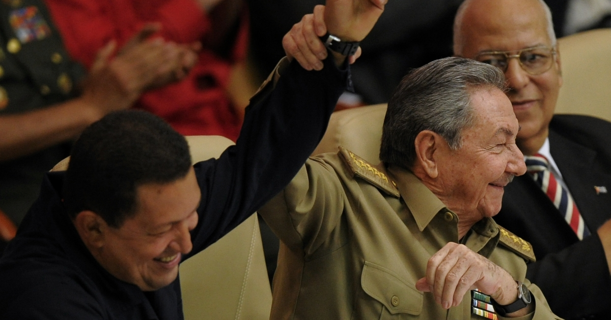 Cuban President Raul Castro lifts the arm of Venezuelan President Hugo Chavez at a gathering of leftist Latin American leaders in Havana in November 2010.</p>