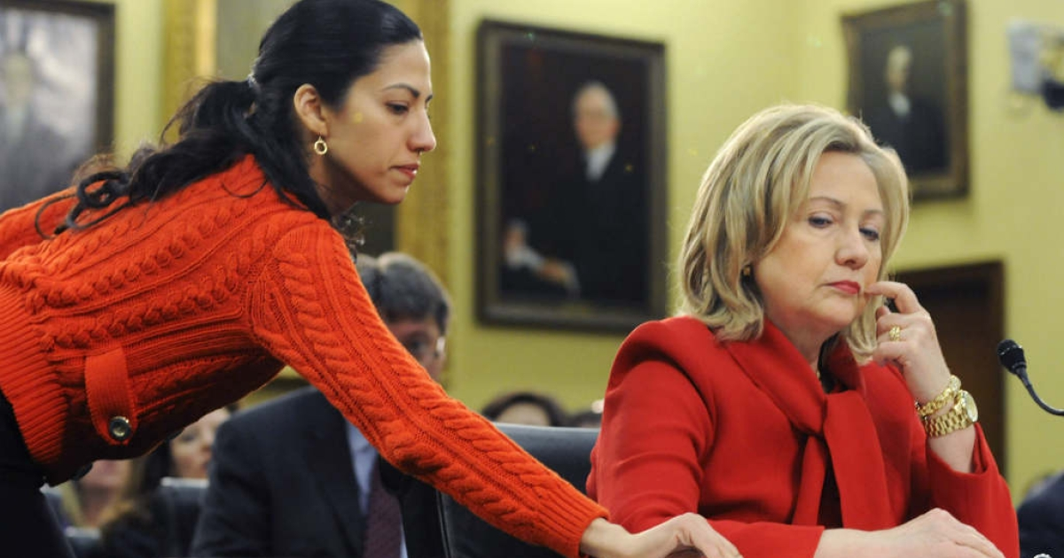 Huma Abedin (L) hands U.S. Secretary of State Hillary Clinton (R) receives a note.</p>