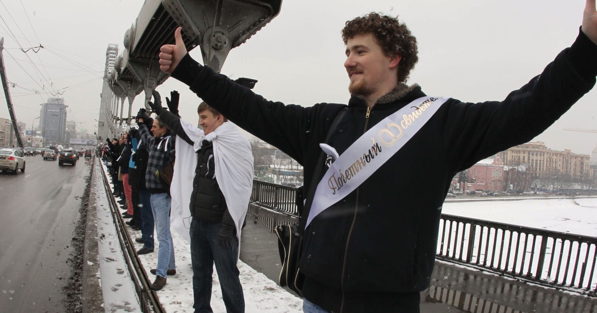Russian opposition supporters, holding white ribbons, form a chain around Moscow on February 26. A din of endless honking descended on the capital's 16-kilometer Garden Ring road as drivers expressed support for the protesters.</p>