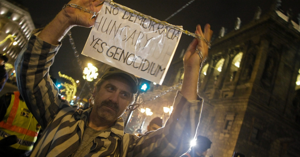 An anti-government demonstrator last night in Budapest</p>