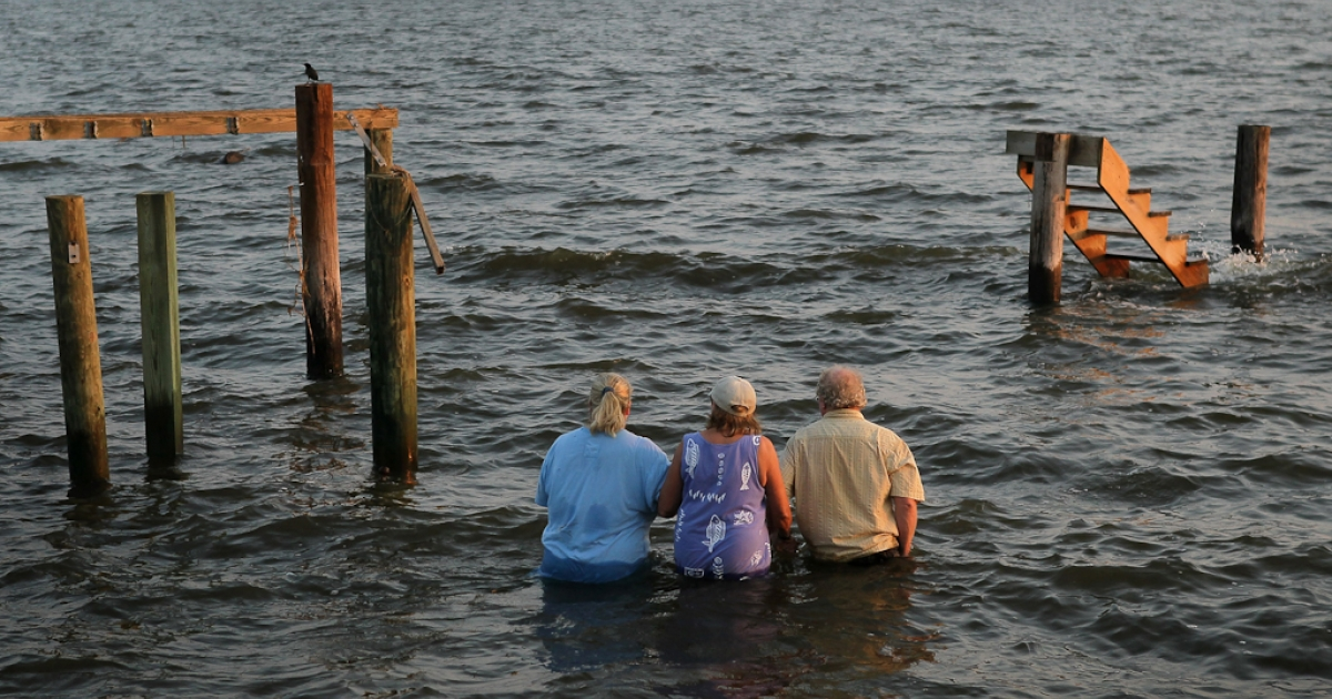 Billy Stinson, his wife Sandra Stinson and daughter Erin Stinson walk out to watch the sunset from the steps where their cottage once stood August 28, 2011 in Nags Head, North Carolina. The cottage, built in 1903 and destroyed yesterday by Hurrican Irene, was one of the first vacation cottages built on Albemarle Sound in Nags Head.</p>