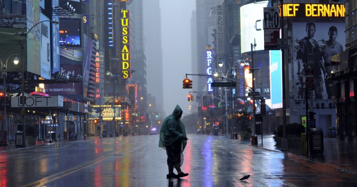 A man walks across 42nd Street in Times Square in New York on August 28, 2011 as Hurricane Irene hits the city and Tri-State area with rain and high winds. A weakened Hurricane Irene tore Sunday into New York, hammering Manhattan's skyscrapers with fierce winds and threatening to flood the financial district after killing at least nine people along the US east coast.</p>