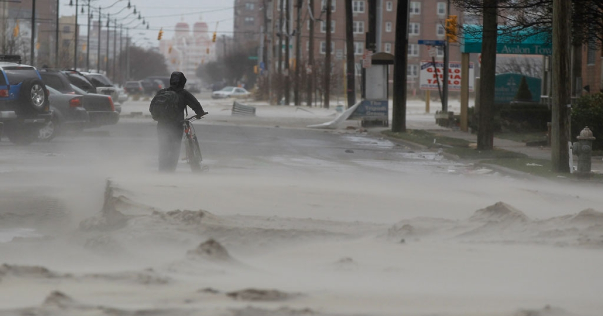 A man walks down a street covered in beach sand due to flooding from Hurricane Sandy on October 30, 2012 in Long Beach, New York.</p>