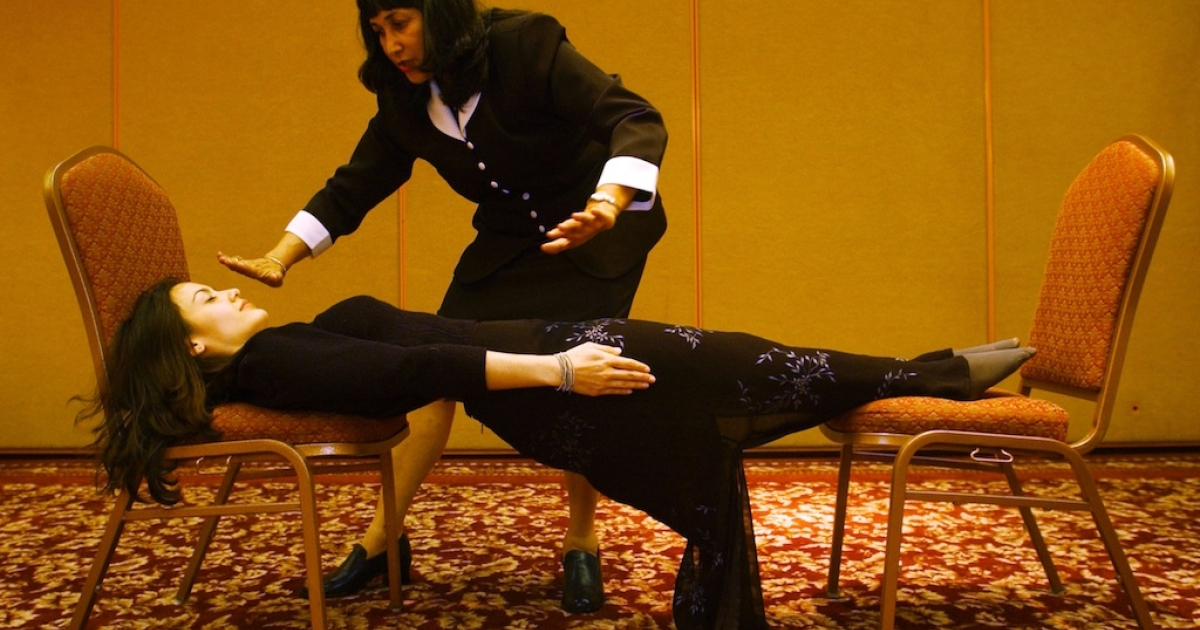 Hypnotherapist and actress Cathy Kay is stretched between chairs after becoming rigid as a board under the hypnotic suggestion of Shelley Stockwell, president and founder of the International Hypnosis Federation &amp; Creativity Institute, at the International Hypnosis Federation''s Mind, Body, Spirit, Fun Conference, July 20, 2001 in Long Beach, CA.</p>