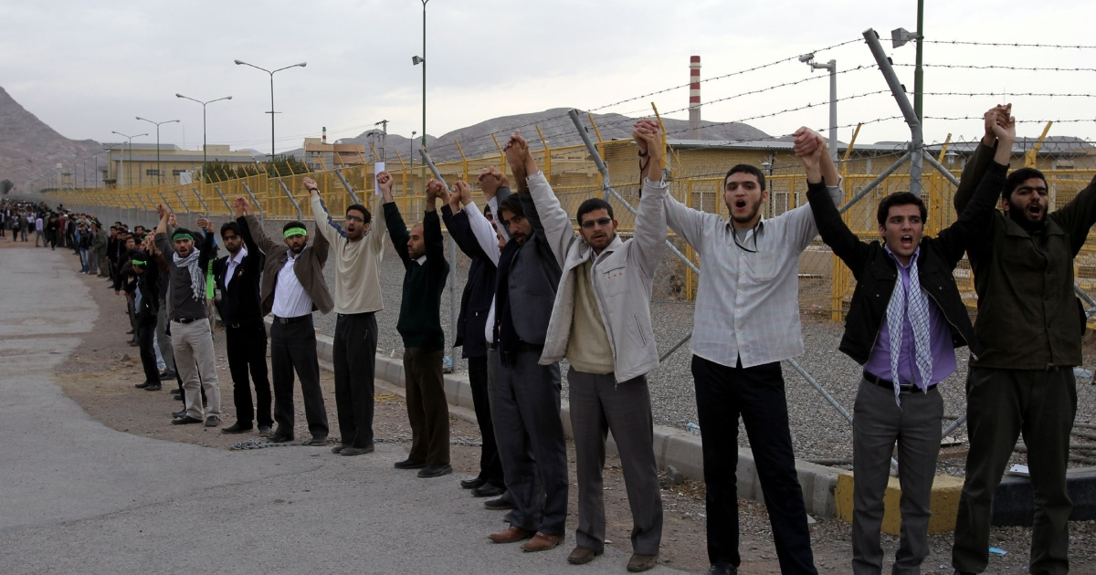 Iranian students shout slogans as they form a human chain outside the Isfahan Uranium Conversion Facility during a protest in the city in support of Iran's nuclear program and against military threats by Israel on Nov. 15, 2011.</p>
