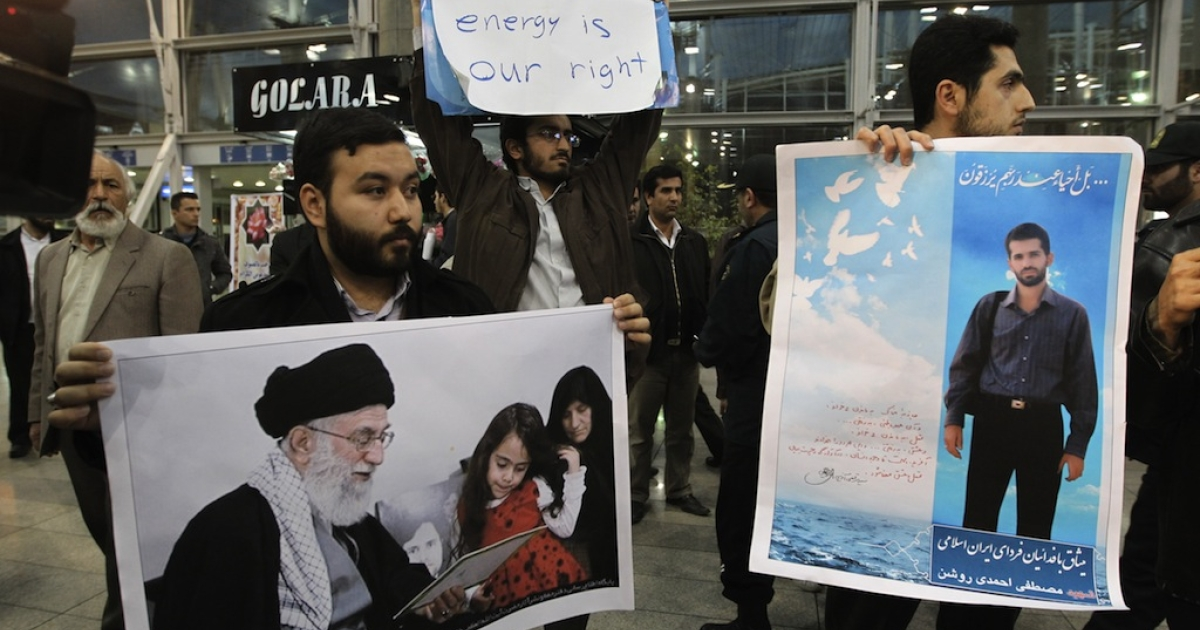 Iranian students hold a poster of assassinated nuclear scientist Mostafa Ahmadi-Roshan (R) and a picture of the family of killed nuclear scientist Dariush Rezaei with Iran's supreme leader Ayatollah Ali Khamenei as they protest at the Imam Khomeini airport in Tehran on January 29, 2012 during the arrival of the International Atomic Energy Agency (IAEA) inspectors.</p>