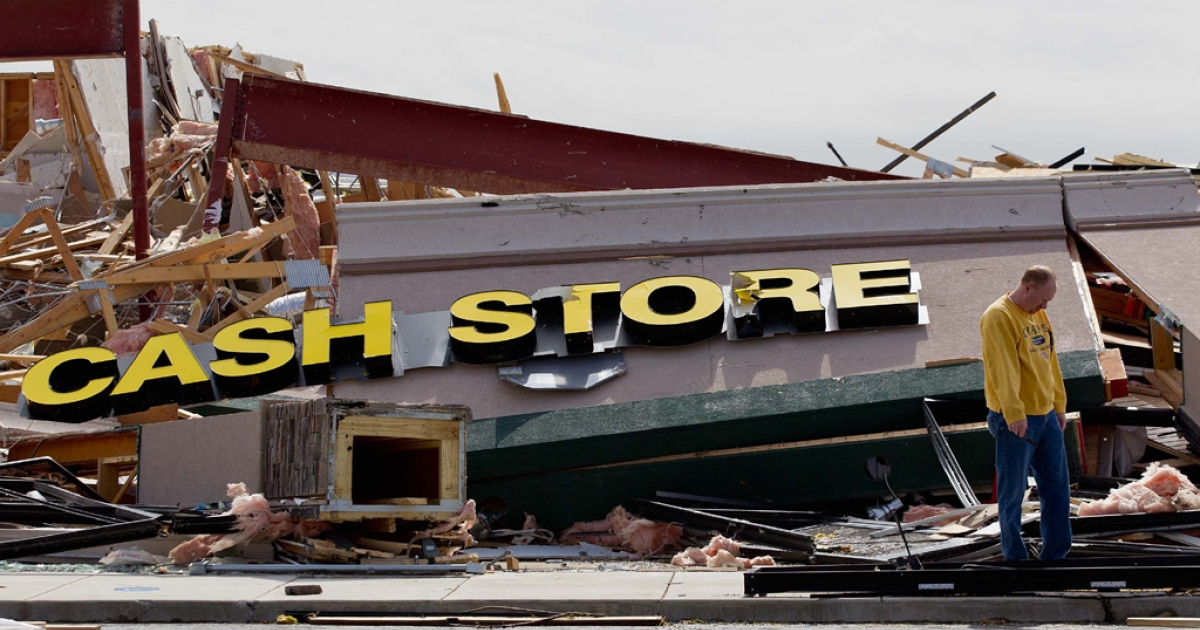 John Bonenberger looks at debris after a tornado damaged a strip mall where his bussiness was located Feb., 29, 2012  in Harrisburg, Ill. According to reports, at least nine people were killed in tornadoes across the Midwest. (Photo by Whitney Curtis/Getty Images)</p>
