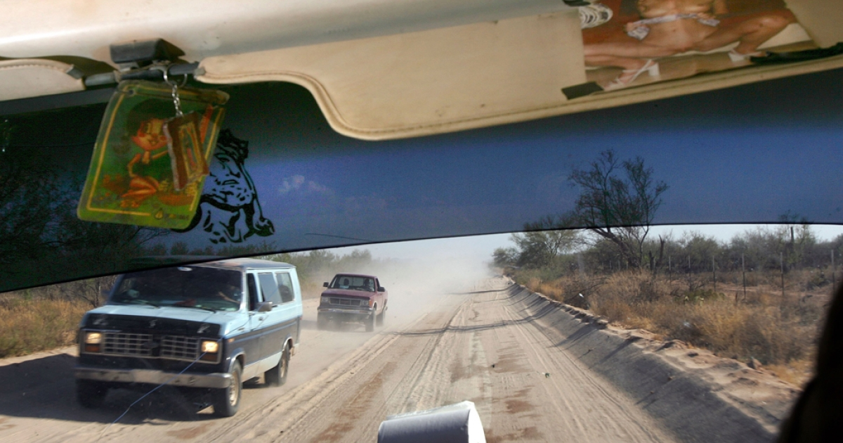 Immigrant transport vans pass one another on the dirt toll road that leads to the border north of Altar, Mexico.</p>