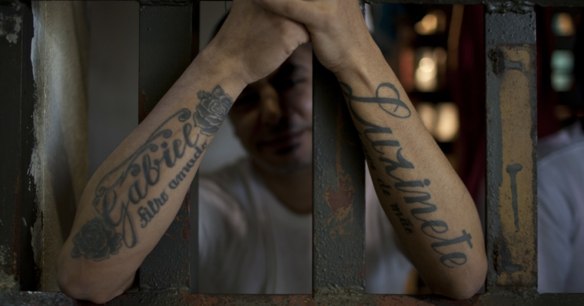 An inmate of an unauthorized holding center is apprehensive about an impending transfer to a new facility. His arms are tattooed with dedications to his son and mother.</p>