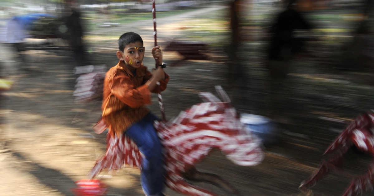 A Bangladeshi child rides on a merry-go-round.</p>
