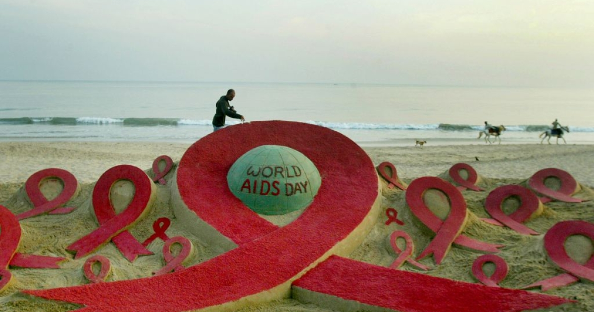 Horses canter past an AIDS-awareness sand sculpture on Golden Sea beach in Puri, India.</p>