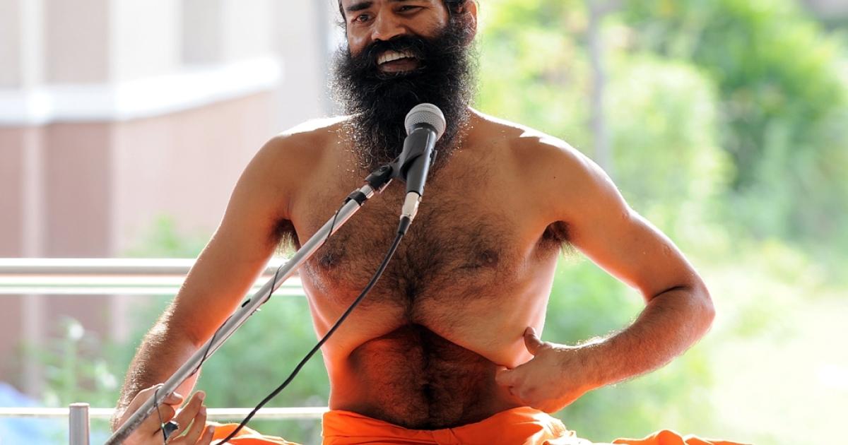 Indian guru Swami Baba Ramdev performs yoga during his hunger strike at the Pitanjali Yogpeeth in Haridwar on June 7, 2011.</p>