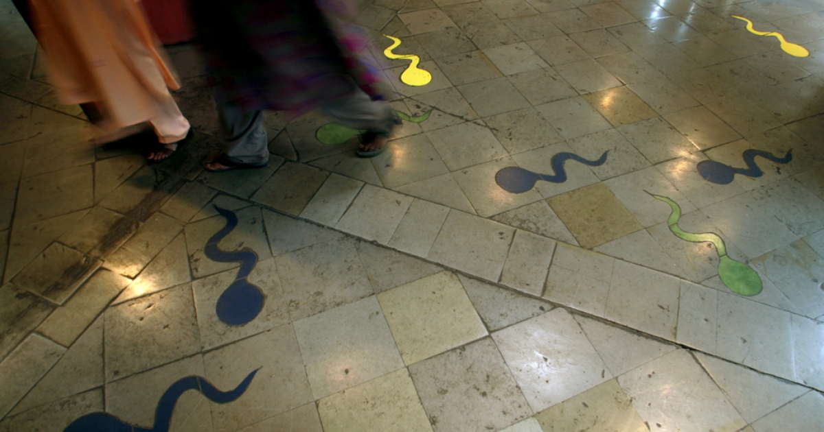 Women walk alongside drawings of sperms at Sexual Health Information Art Gallery in Mumbai, India, Feb. 9, 2007.</p>