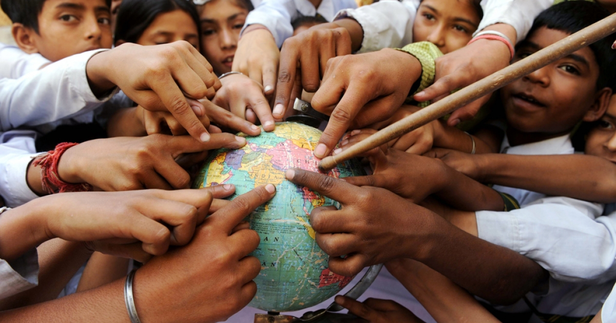 Indian school children in Amritsar point to India on a globe on Earth Day, April 22, 2010.</p>