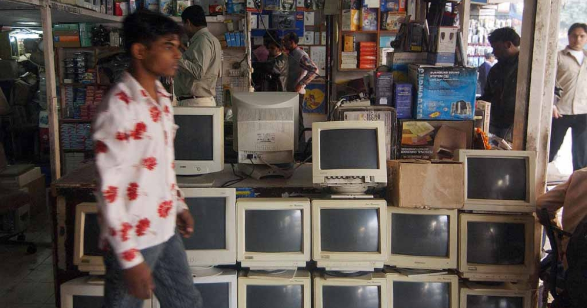 An Indian man walks past old computer screens outside a shop in New Delhi's largest computer market at Nehru Place.</p>