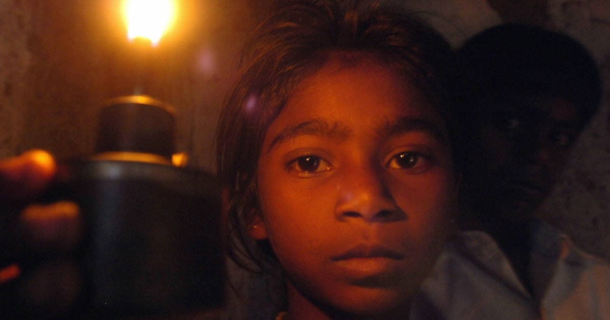 A girl with a kerosene lamp inside her house in Obelahalli village, about 80 kilometres (49.6 miles) north of Bangalore, 03 July 2005.</p>