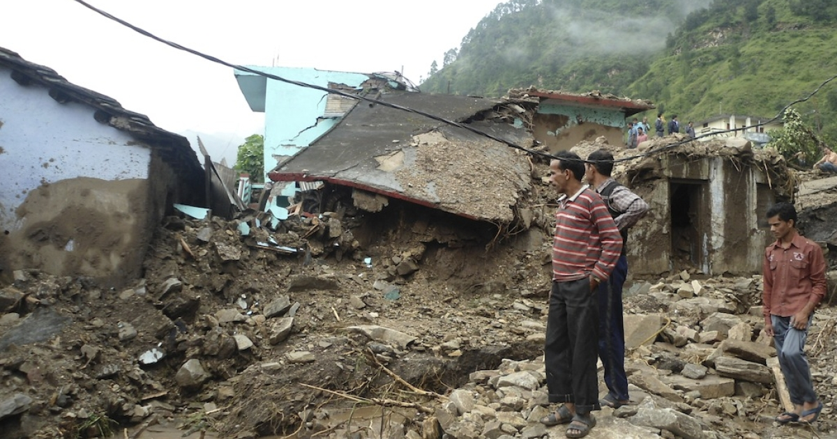 Villagers look at their collapsed homes caused by landslides following heavy rains in Rudyaprayag, India's northern Uttarakhand state, on September 14, 2012. At least 45 people in northern India died on Friday in landslides and flashfloods triggered by heavy overnight monsoon rains and about a dozen others are missing, a rescue official told AFP.</p>