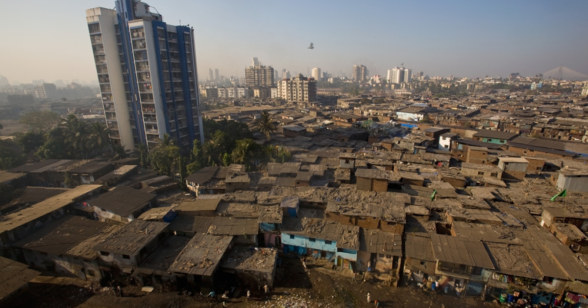 Men recycle waste on rooftops in Dharavi slum on Feb. 3, 2009 in Mumbai.</p>