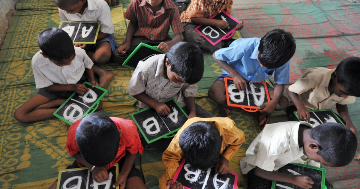 Indian schoolchildren write English alphabets on slates at a government primary school in the outskirts of Hyderabad on June 13, 2011.</p>