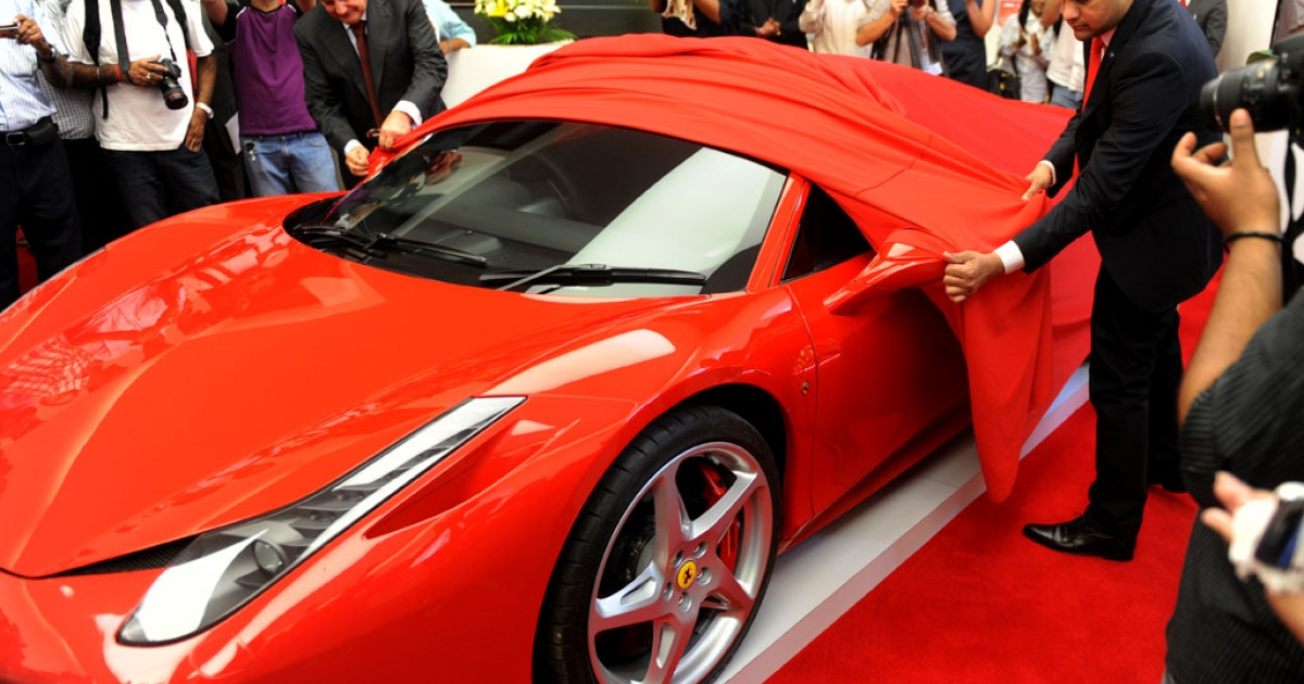 CEO of Ferrari SPA, Amadeo Felisa (left), and the chairman of Shreyans Group, Ashish Chordia (right) unveil a Ferrari 458 during the launching of its first dealership in India on May 26, 2011.</p>