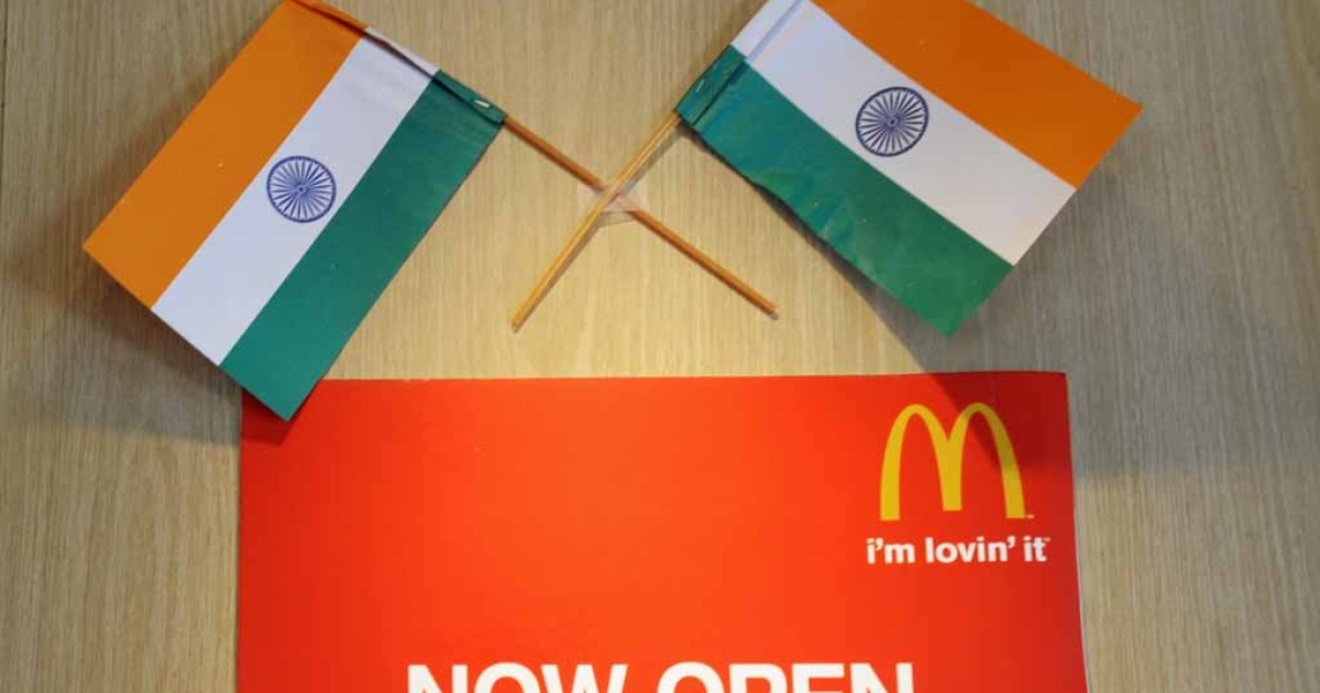 Two Indian flags adorn a sign at a local McDonalds chain restaurant in New Delhi.</p>