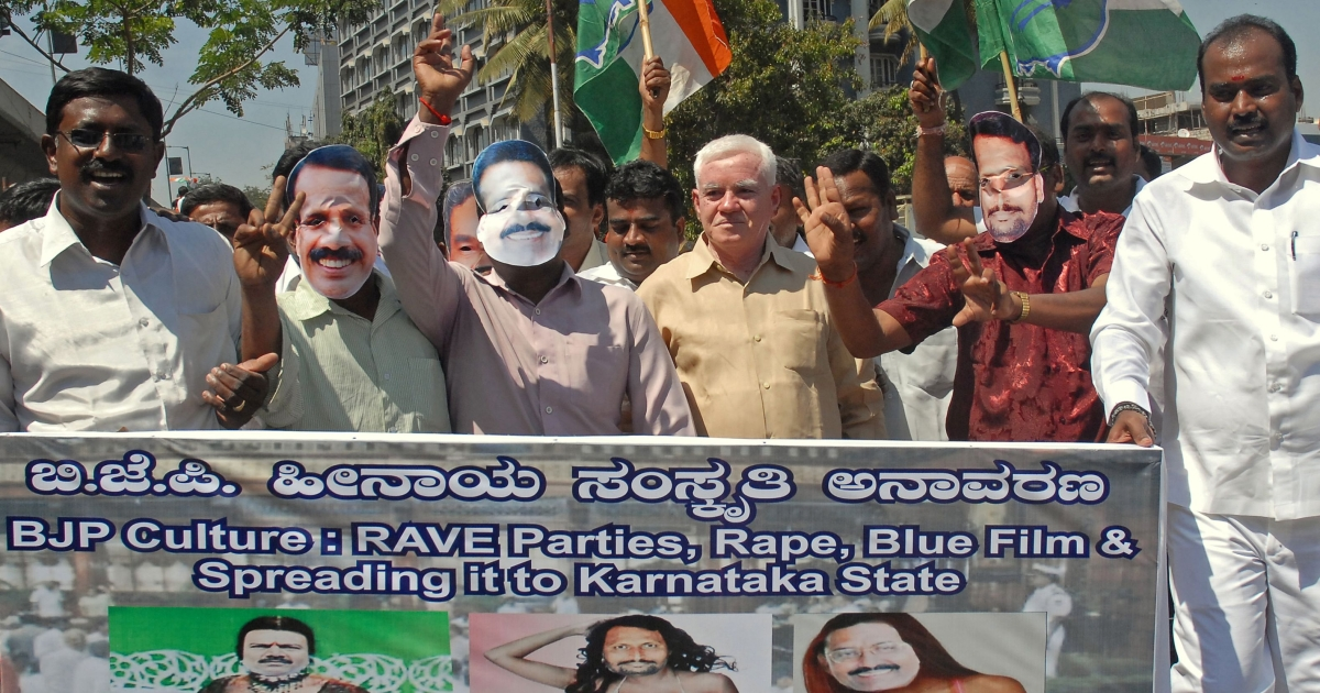 Protesters from the Karnataka State Youth Congress in Bangalore hold a poster of the three BJP members involved in a mobile phone porn scandal.</p>