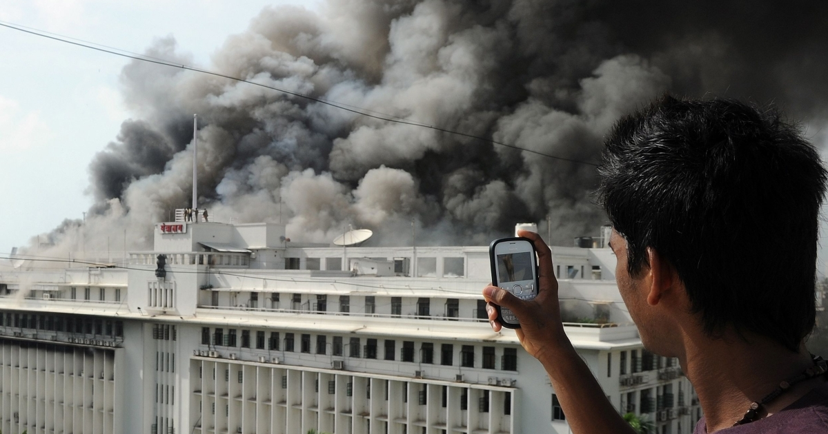 An onlooker uses his mobile phone to take pictures of the burning Mantralaya building, which houses the Maharashtra state secretariat, in Mumbai on June 21, 2012.</p>