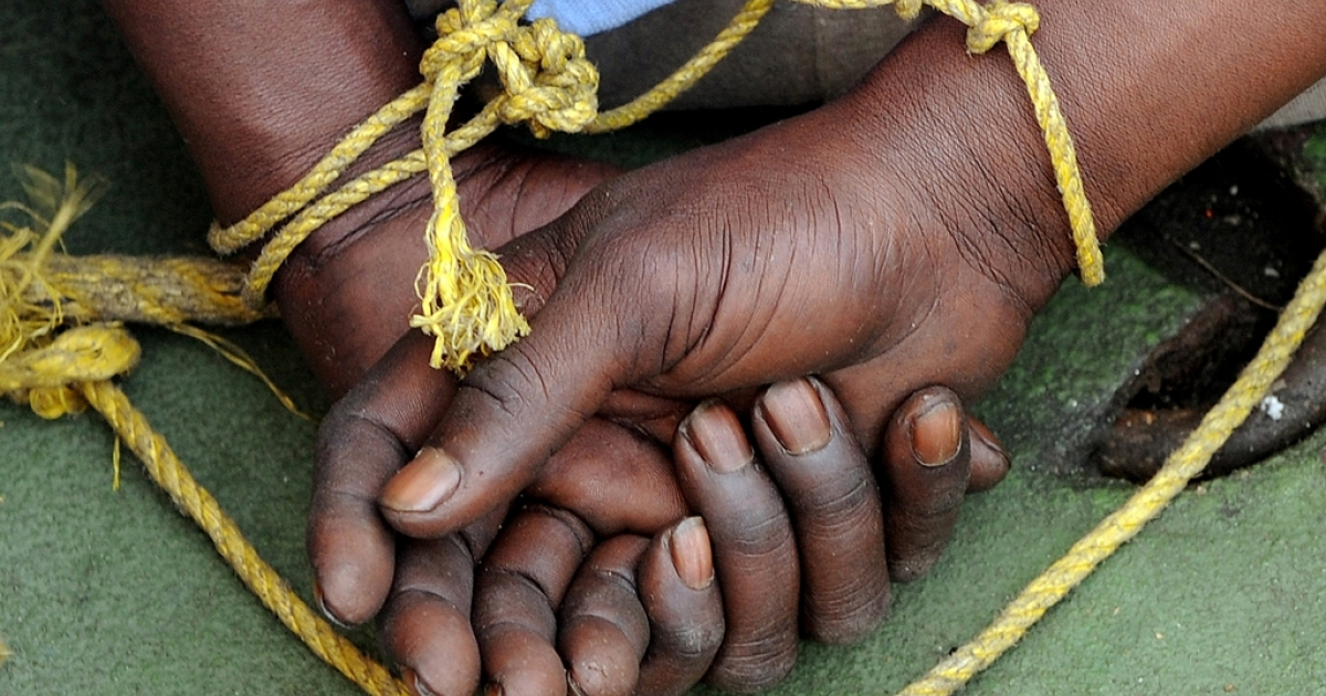 A suspected Somali pirate's hands are tied behind his back during a media interaction on board an Indian Coast guard ship off the coast of Mumbai on Feb. 10, 2011.</p>