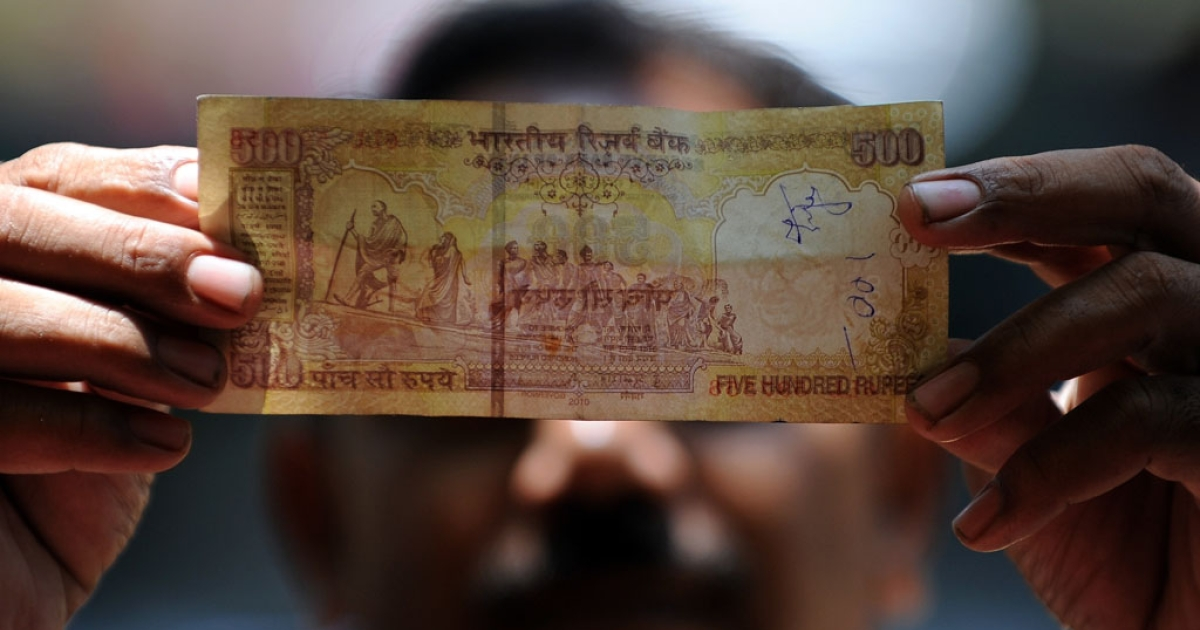 A shopkeeper holds a 500 rupee note at a roadside food stall in Mumbai on May 7, 2012.</p>