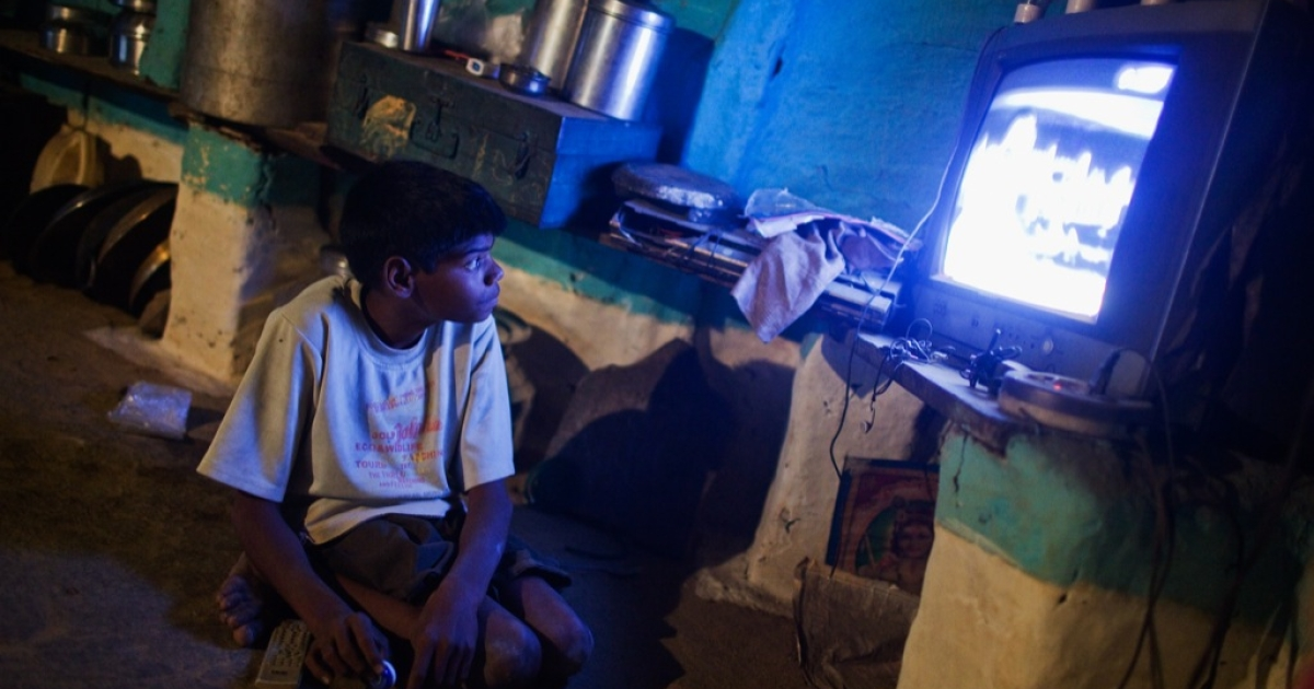 Fifteen year old Sachin Kumar watches television in his home located in a slum near the site of the deserted Union Carbide factory on November 30, 2009 in Bhopal, India.</p>