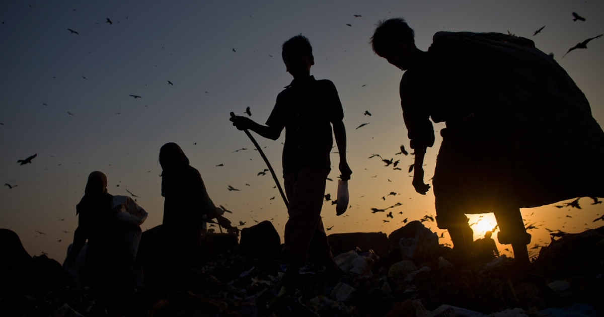 Indian rag pickers sort through garbage.</p>