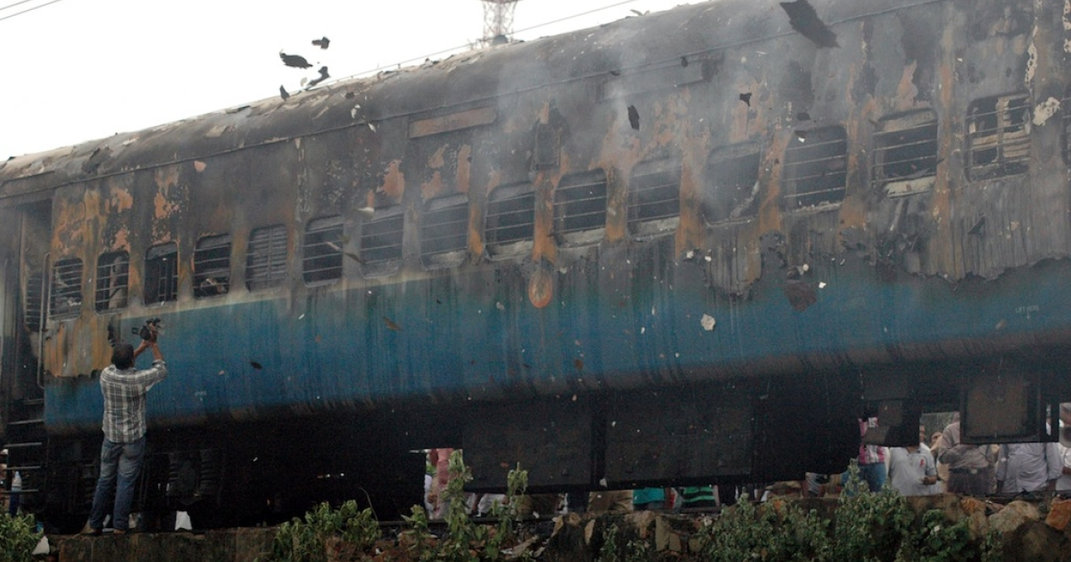 A videojournalist (L) records footage of a gutted train carriage, which caught fire from an electrical short circuit killing as man as 47, in Nellore, India, on July 30, 2012.</p>
