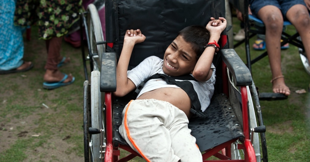 An Indian disabled child suffering from the effects of the 1984 Bhopal disaster, reacts in discomfort while waiting to participate in a march during a 'Special Olympics' in Bhopal on July 26, 2012</p>