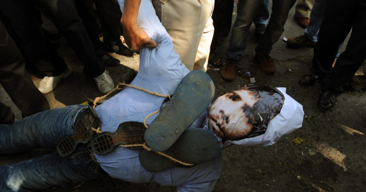 An Indian policeman confiscates an effigy of Pakistan-born Mohammed Kasab, who was the sole surviving gunman of the 2008 Mumbai attacks, as activists celebrate his execution in Mumbai on November 21, 2012.</p>