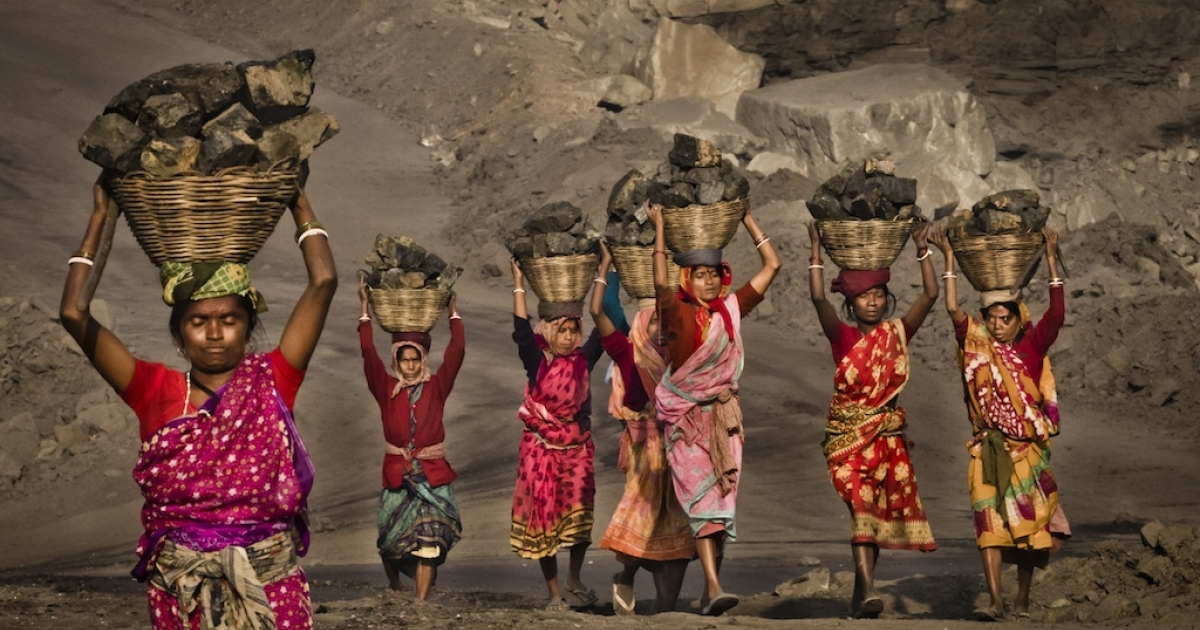 Villagers carry coal near Jharia, India. India's coalition government has been accused of losing $210 billion in potential revenues by selling coal fields to top industrialists, which has contributed to India's electricity problems.</p>