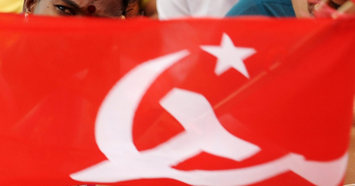 A Communist flag flutters as Indian opposition and left activists demonstrate against the price hike of essential commodities during a protest rally in Bangalore on April 27, 2010.</p>