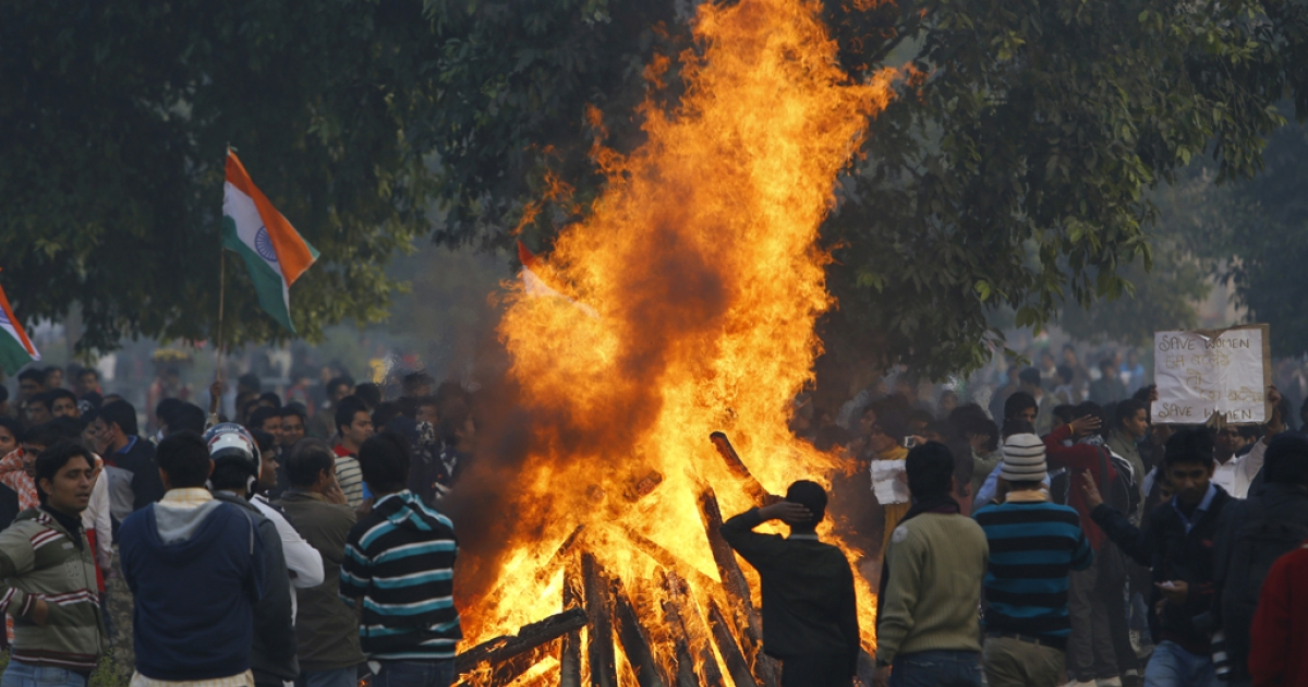 Indian demonstrators set fire to wooden barricades during a protest calling for  better safety for women following the rape of a student last week, in front the India Gate monument in New Delhi on December 23, 2012. In the biggest protest so far, several thousand college students rallied at the India Gate monument in the heart of the capital where they were baton-charged, water cannoned and tear gassed by the police.</p>