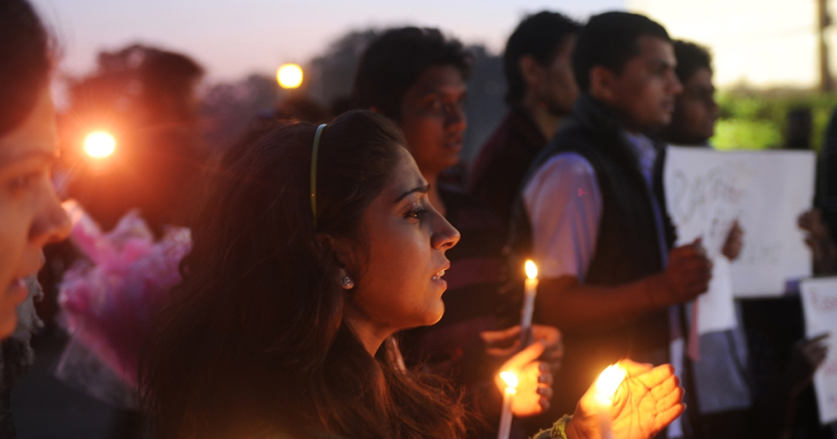 Indian students and activists carry candles at India Gate during a protest following the gang-rape of a student in New Delhi on December 19, 2012.</p>