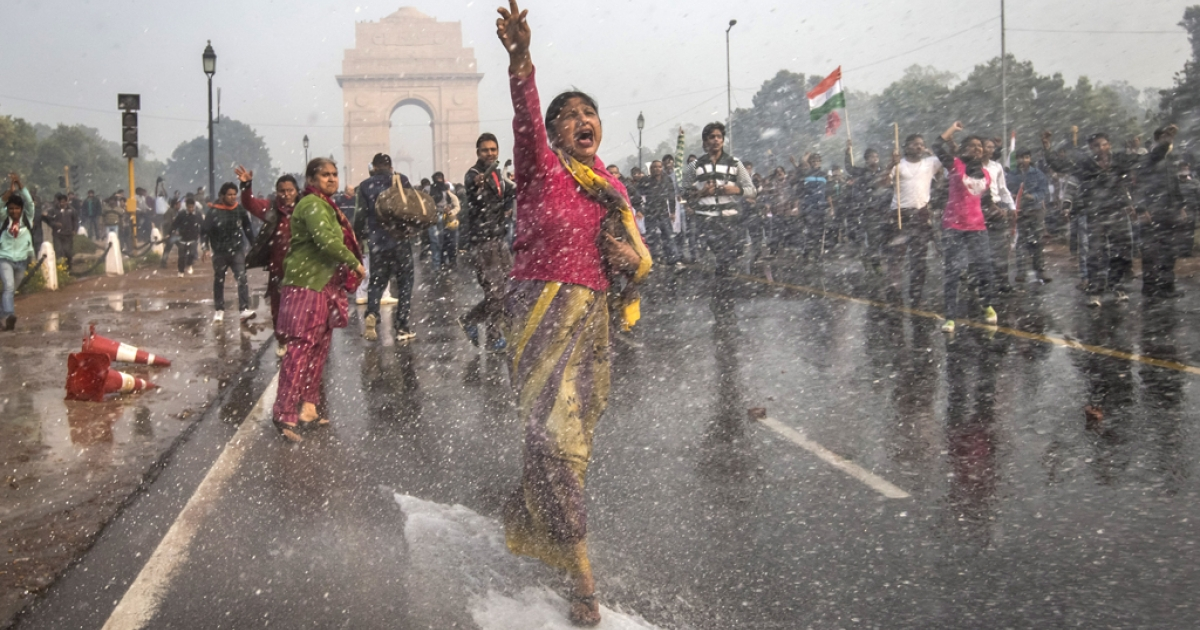 A protestors chants slogans as she braces herself against the spray fired from Police water canons during a protest against the Indian governments reaction to recent rape incidents in India, in front of India Gate on December 23, 2012 in New Delhi, India. The gang rape of a 23-year-old paramedical student in a moving bus on December 16, in Delhi, has led to people to react openly against the governments current rape laws. Over a thousand protesters gathered in front of Delhi to protest against lax laws and the governments handling of recent rape cases all over India.</p>